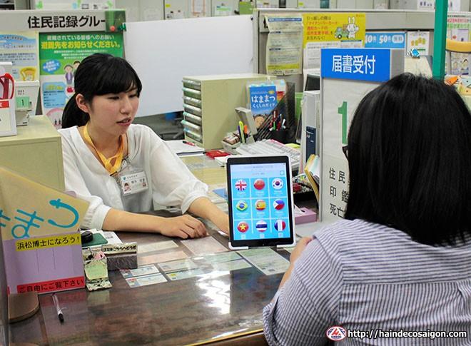 Một nhân viên tại chính quyền thành phố Hamamatsu ở tỉnh Shizuoka cho thấy các dịch vụ phiên dịch trên máy tính bảng để trả lời một cư dân nước ngoài